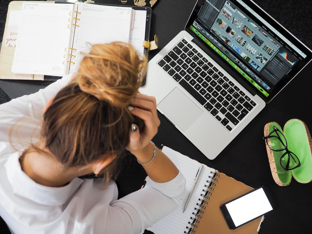 パソコンの前で「商用イラストがいいのか、ストックイラストがいいのか…」と頭を抱える女性