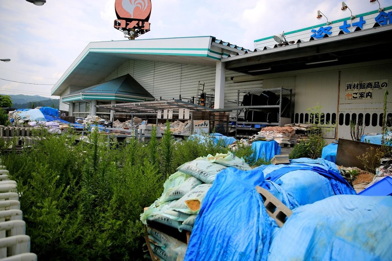 4年以上放置されたホームセンターは雑草に埋もれている(2015年7月31日、福島県飯舘村)