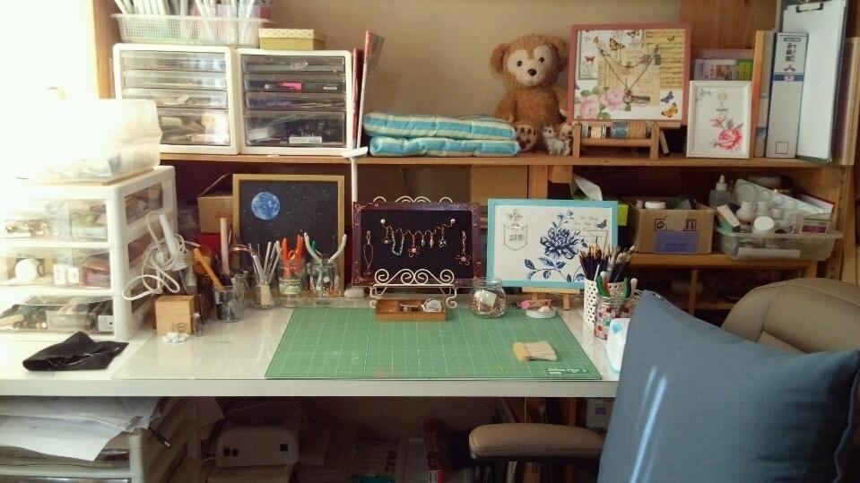アクセサリーやらイラストやら何やらを制作する作業部屋です。家の一番奥の隅っこにある三畳ほどの部屋。台所の隣。西陽が射します。机の後ろの棚の真ん中にクッション